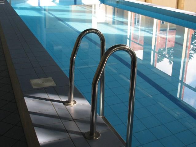 Spokojna tafla wody w basenie. Na pierwszym planie drabinka