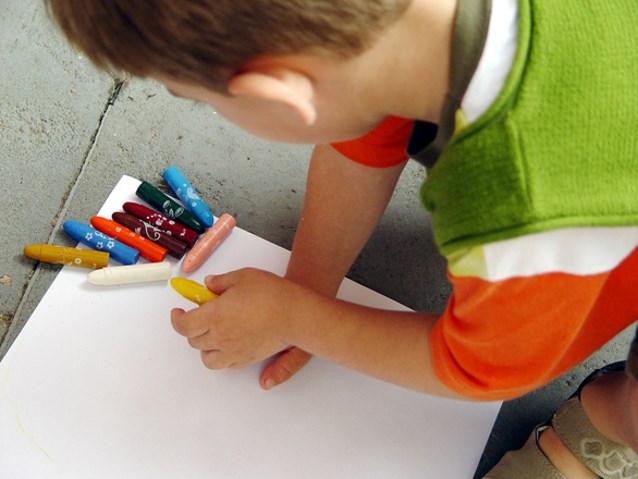 Chłopiec rysuje kolorowymi kredkami