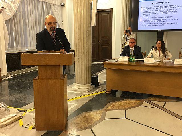 Mirosław Przewoźnik stoi przy mównicy przed mikrofonem, w tle dwie osoby za stołem prezydialnym