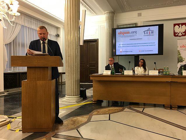 Przy mównicy stoi i przemawia Tomasz Przybyszewski, w tle dwie osoby za stołem prezydialnym w eleganckiej sali