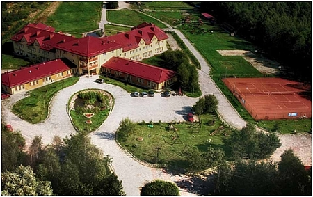 Widok z góry na dość duży budynek z czerwonym dachem, obok parking i dwa korty tenisowe