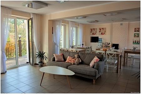 Salon z kanapą, stolikiem, stołami i krzesłami, po lewej otwarte okno