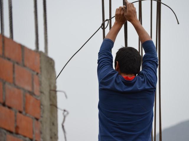mężczyzna tyłem odwrócony trzyma drut, pracuje przy budowie, powstaje mur z czerwonej cegły