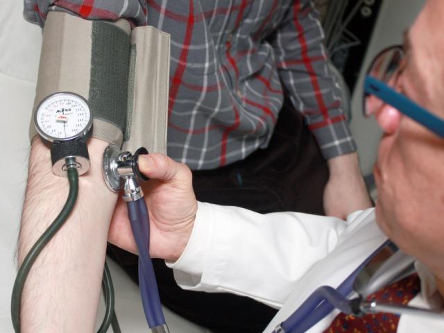 lekarz mierzy ciśnienie mężczyźnie widać tylko jego rękę i koszulę w szaro czerwoną kratę