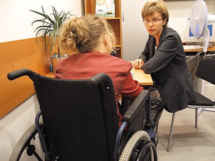Biuro. Kobieta siedząca przy biurku rozmawia z kobietą siedzącą na wózku
